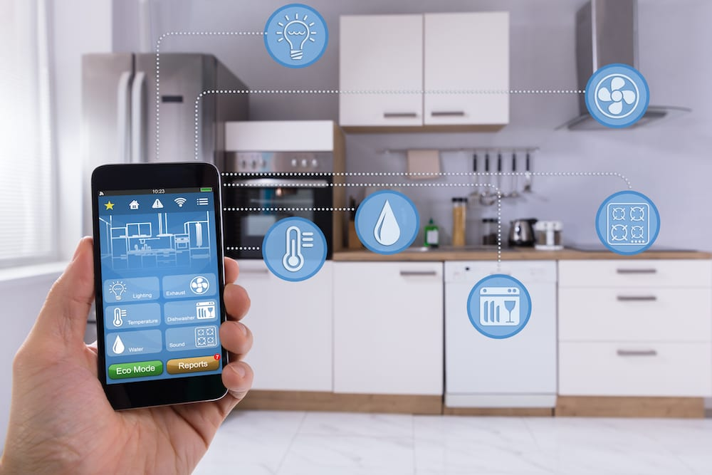 Close-up Of A Person's Hand Using Smart Home Application On Smartphone In Kitchen