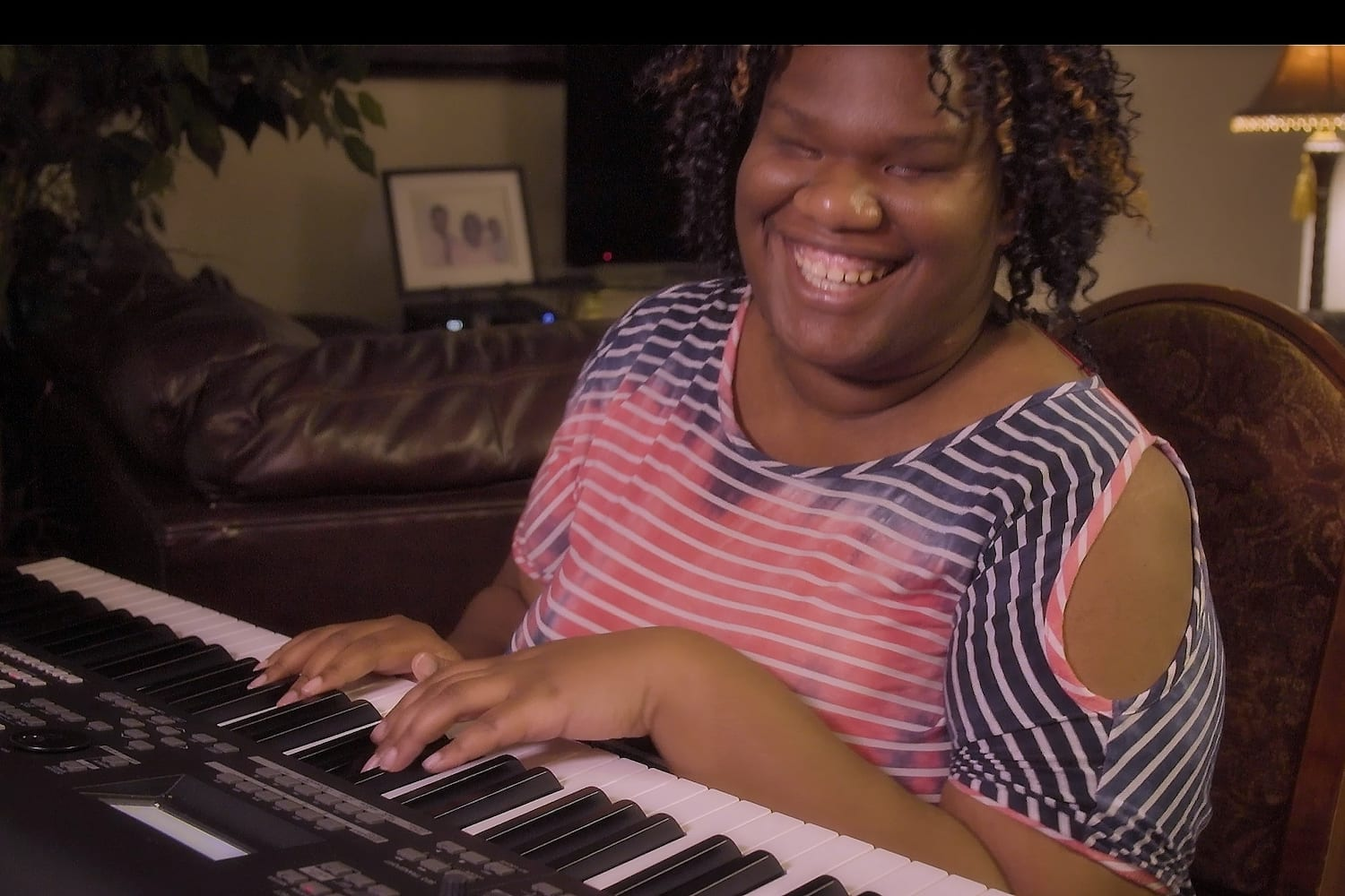 Photo of Alexandria playing the piano, a NWAF loan helped pay for her BrailleNote Touch